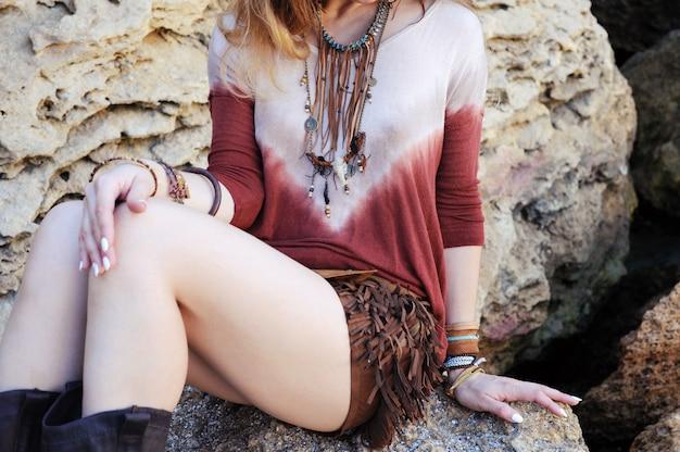 Pescoço, peito e mãos femininos com pulseiras boho chic e colar de couro