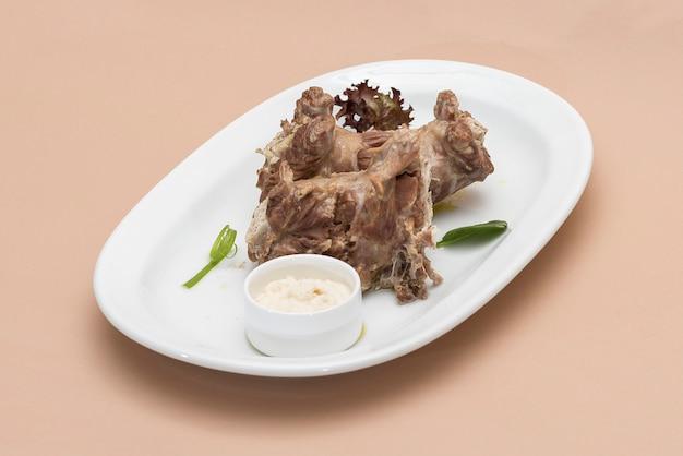 Pescoços de peru, servido com purê de rábano, colocado na chapa branca, luz de fundo, isolado