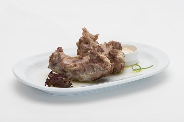 Pescoços de peru, servido com purê de rábano, colocado na chapa branca, luz de fundo