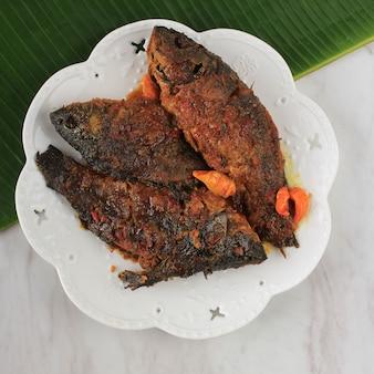 Pesmol fish usando goldfish. adicione o peixe frito à frigideira. pesmol, receita típica de peixe de java ocidental, indonésia, com sabor doce, azedo e picante