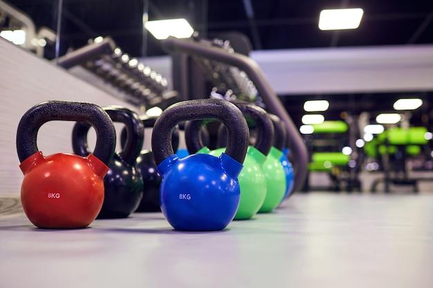 Pesos de kettlebell esportes no chão no ginásio