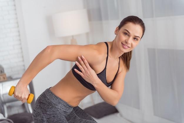 Pesos de mão favoritos. bela alerta atlética jovem de cabelos escuros sorrindo e segurando um peso na mão enquanto pratica esportes