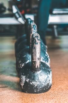 Pesos e dumbbells velhos no gym no assoalho.