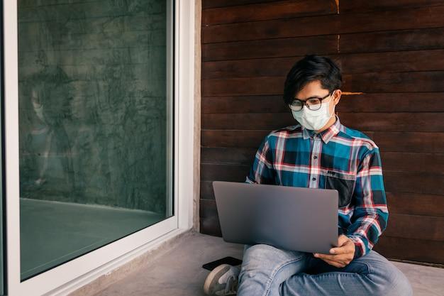 Pesquisa de emprego de homem asiático na internet, homem em casa à procura de uma boa carreira, conceito de crise econômica, desemprego e produção de pessoas, surto de doença de coronavírus 2019 ou covid-19.