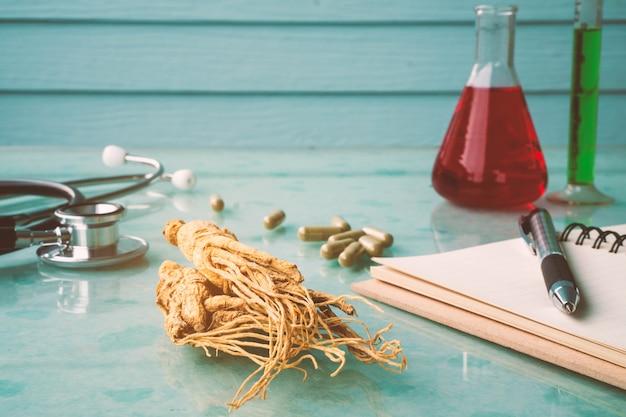 Pesquisa de ginseng para uma boa saúde com estetoscópio, caderno, caneta e tubo de ensaio.