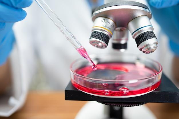 Pesquisa de trabalho do bioquímico cientista asiático com um microscópio no laboratório