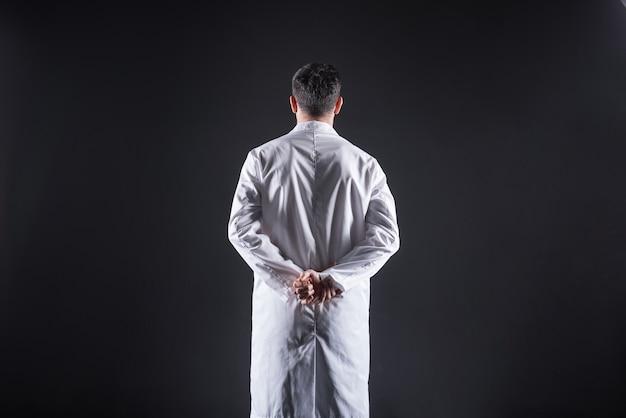 Pesquisa inovadora. homem simpático e inteligente, usando um jaleco e segurando as mãos atrás das costas enquanto trabalha em um laboratório moderno