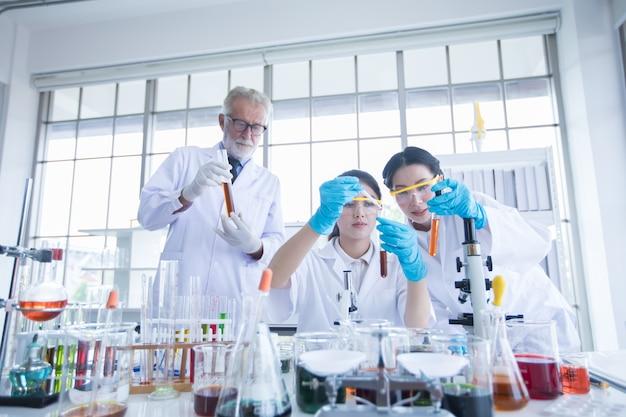 Pesquisa médica e cientistas estão trabalhando com um microscópio e um tablet e tubos de ensaio,