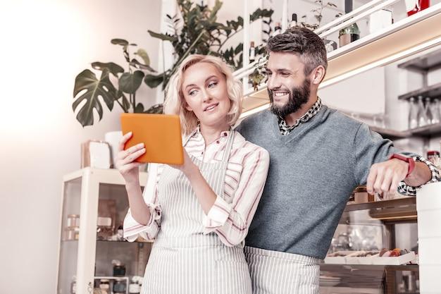 Pesquisa na internet. mulher agradável e agradável em pé com o namorado enquanto procura as informações