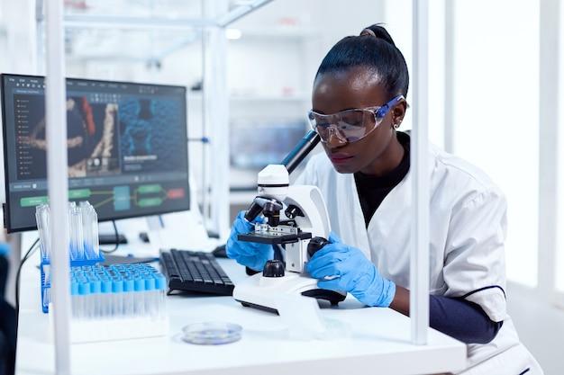 Pesquisador africano ajustando lentes de microscópio olhando amostra em lâmina de vidro. cientista negro da saúde no laboratório de bioquímica, usando equipamento esterilizado.