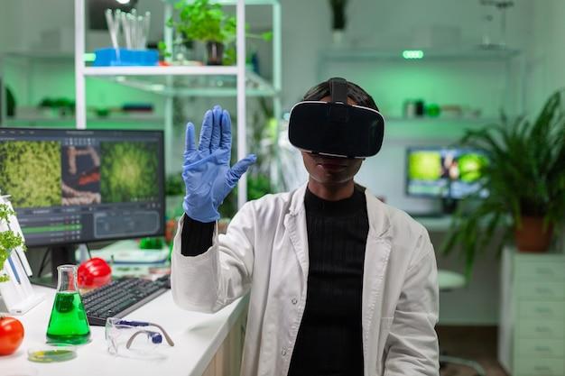 Pesquisador biólogo africano com fone de ouvido de realidade virtual pesquisando novo experimento genético