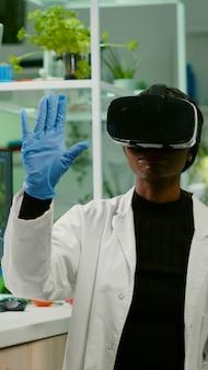 Pesquisador biólogo com fone de ouvido de realidade virtual pesquisando novo experimento genético para especialização em microbiologia