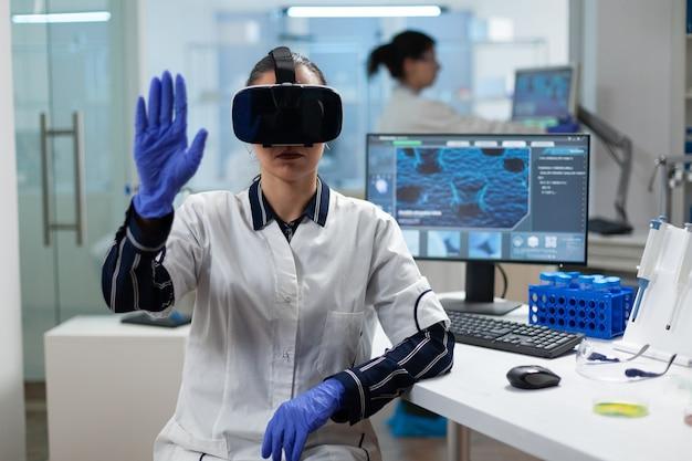 Pesquisador biólogo usando fone de ouvido de realidade virtual examinando experimento de bioquímica