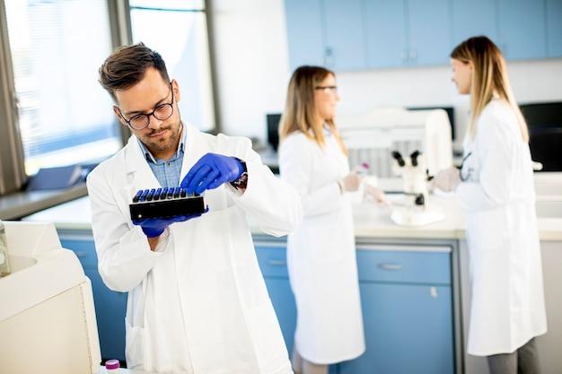 Pesquisador bonito em roupas de trabalho de proteção em pé no laboratório e analisando amostras de líquidos