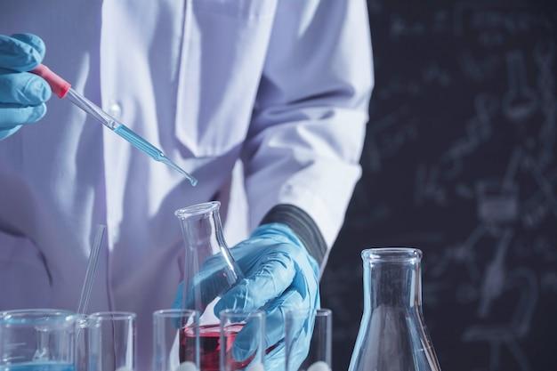 Pesquisador com tubos de ensaio químico de laboratório de vidro com líquido para pesquisa analítica, médica, farmacêutica e científica.