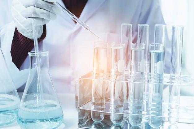 Pesquisador com tubos de ensaio químicos de laboratório de vidro com líquido para análise