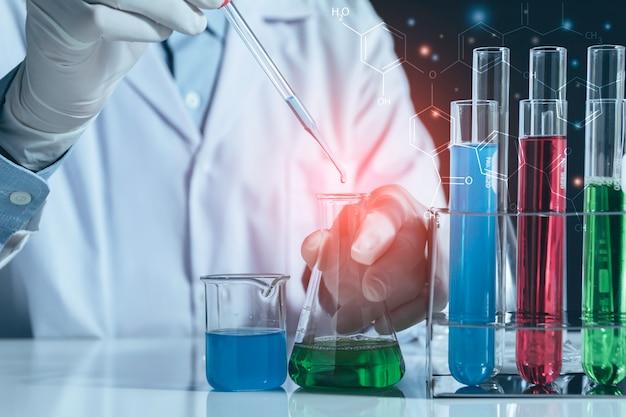 Pesquisador com tubos de ensaio químicos de laboratório de vidro com líquido para o conceito de pesquisa analítica, médica, farmacêutica e científica.