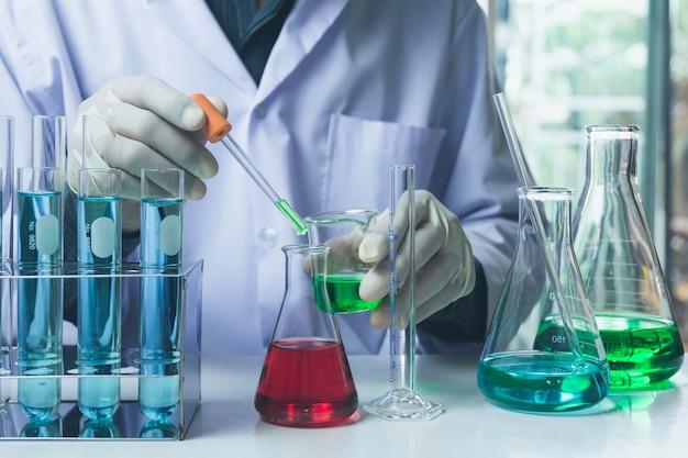 Pesquisador com tubos de ensaio químicos de laboratório de vidro com líquido