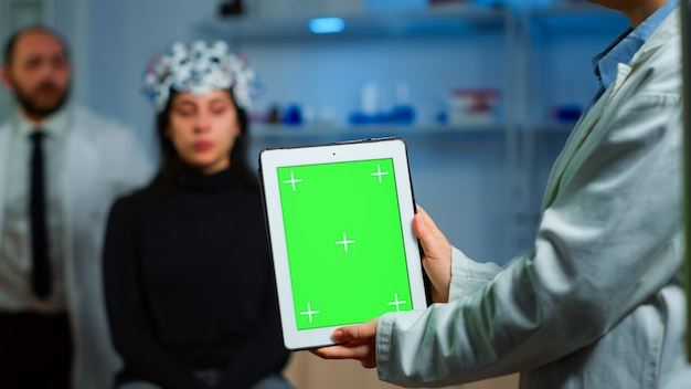 Pesquisador de cuidados de saúde segurando e olhando para um tablet com visor de chroma key no laboratório neurológico. equipe de cientistas fazendo pesquisas médicas, lendo em um dispositivo com tela verde, display de maquete isolado