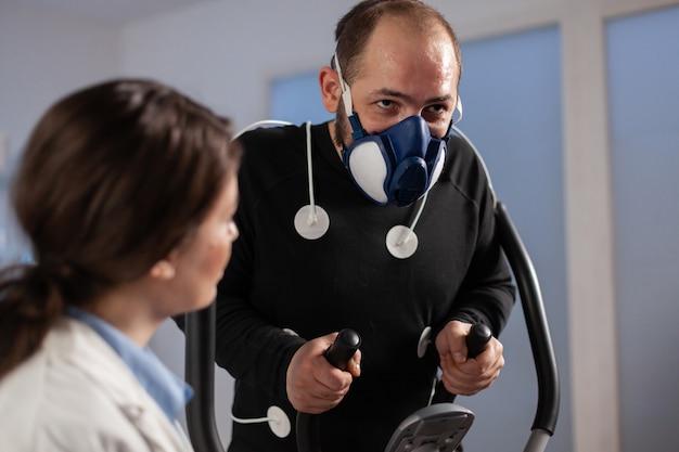 Pesquisador de fitness monitorando o desempenho do atleta com sensores conectados em execução no treinamento cruzado. cientista de fitness no laboratório de ciências do esporte. eletrodos ecg no corpo.