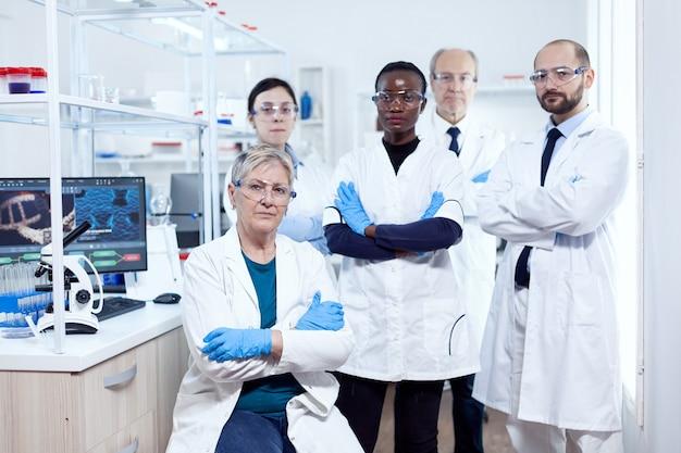 Pesquisador de saúde no local de trabalho em pé com os braços cruzados. cientista africano da saúde no laboratório de bioquímica, usando equipamento esterilizado.