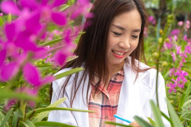 Pesquisador feliz botânica pesquisa orquídea usando um boné branco