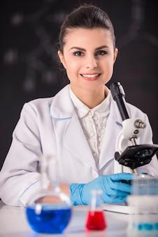 Pesquisador fêmea do doutor da beleza nova que usa o microscópio.