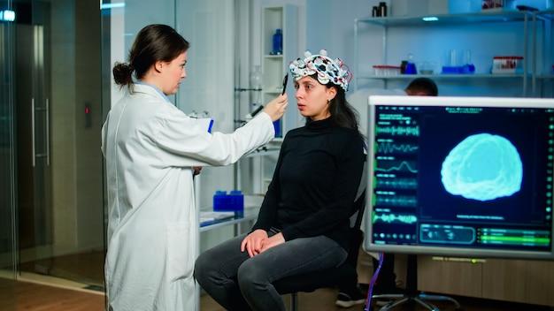 Pesquisador médico em medicina neurológica, preparando o paciente para examinar as funções cerebrais usando ferramentas de alta tecnologia e neurologia para pesquisas científicas em laboratórios de tecnologia avançada
