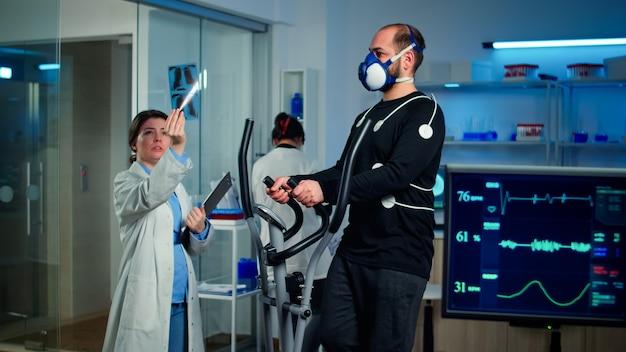 Pesquisador médico examinando a evolução do estado de saúde do atleta, olhando um raio-x enquanto homem com máscara correndo no cross trainer monitorando sua resistência