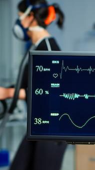 Pesquisador médico examinando imagem de ekg exibida no monitor enquanto o patinete com máscara é executado no cross trainer testando a frequência cardíaca com eletrodos