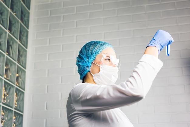 Pesquisador médico segurando tubo de ensaio com líquido fluorescente azul