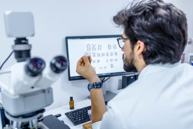 Pesquisador no laboratório olhando na lâmina de microscópio