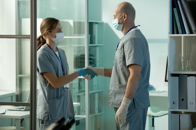 Pesquisador ou clínico bem-sucedido do sexo masculino maduro apertando a mão de sua jovem e bonita assistente enquanto a parabeniza pela invenção da nova vacina