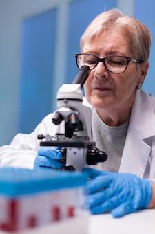 Pesquisador químico sênior de jaleco branco, olhando em microscópio de ponta para experiência em doenças