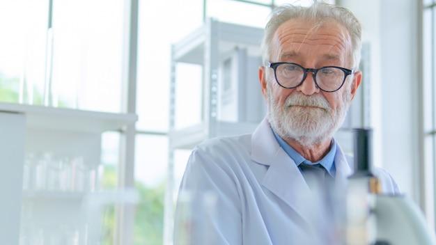 Pesquisador sênior do sexo masculino pensa com concentração facial sobre a pesquisa científica em um laboratório.