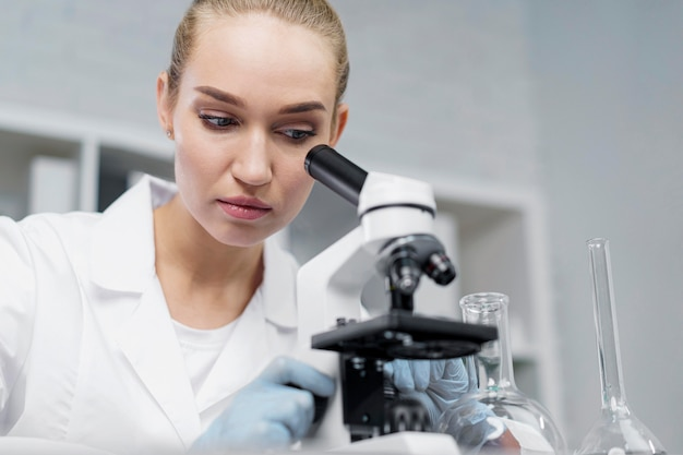 Pesquisadora em laboratório com microscópio