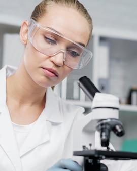 Pesquisadora em laboratório com óculos de segurança e microscópio