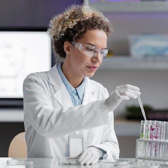 Pesquisadora em laboratório com óculos de segurança e tubos de ensaio
