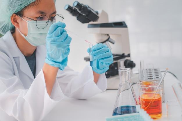 Pesquisadoras do sexo feminino estão experimentando com pipeta, soltando uma amostra em um tubo de ensaio em uma pesquisa experimental em laboratório.