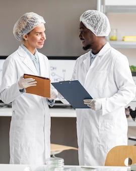 Pesquisadores de smileys no laboratório de biotecnologia com tablet e prancheta