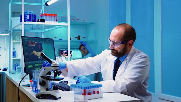 Pesquisadores microbiologistas de biotecnologia trabalhando para o desenvolvimento de vacinas tarde da noite em um laboratório equipado com química