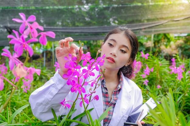 Pesquisadores, mulheres jovens, usando vestidos brancos, conferindo orquídeas e registrando mudanças