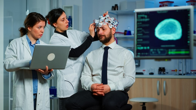 Pesquisadores neurológicos da equipe de mulheres trabalhando juntos desenvolvendo tratamento para o diagnóstico de doença cerebral, explicando resultados de eeg, estado de saúde, funções cerebrais, sistema nervoso e tomografia