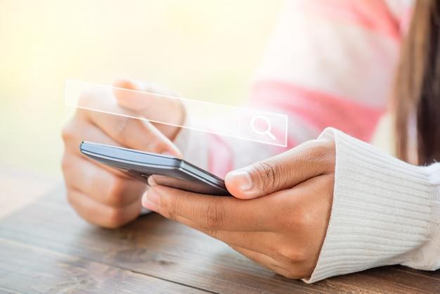 Pesquisando dados de informações sobre o conceito de rede de internet. as mulheres usam smartphones para pesquisar na internet, o que eles estão interessados em. motor de busca com barra de pesquisa em branco.