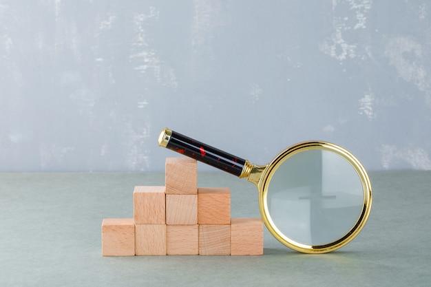 Pesquisando e conceito de negócio com blocos de madeira, vista lateral da lupa.