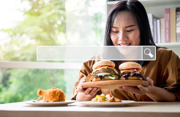 Pesquisando na barra de navegação da internet no fundo, está uma mulher com excesso de peso segurando um transtorno da compulsão alimentar periódica (tcm) de hambúrguer. searching browsing internet data information networking, conceito