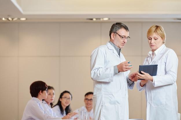 Pesquisas maduras sérias com computador tablet e frasco discutindo o processo de teste de vacina