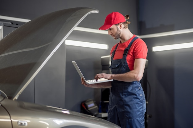 Pesquise informações. homem interessado de macacão olhando para um laptop perto do capô aberto de um carro em uma oficina mecânica