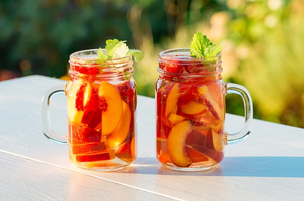 Pêssego cocktail com hortelã no jardim no verão quente, dia ensolarado