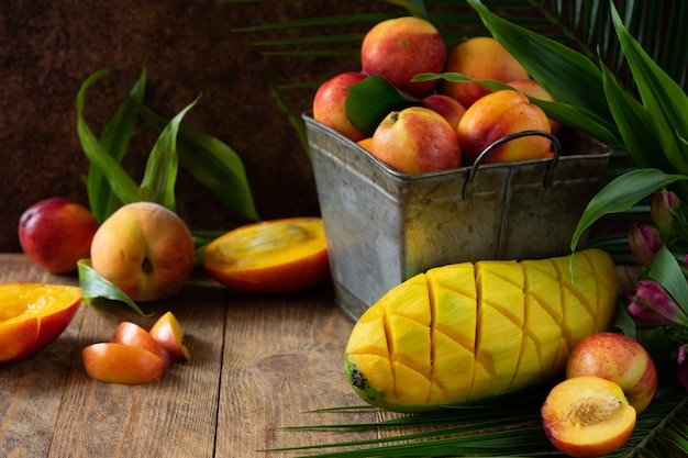 Pêssego e manga frescos e deliciosos na cesta de metal. ingredientes para um smoothie de frutas tropicais